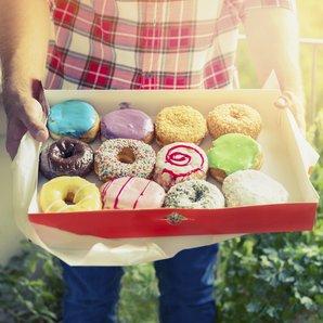 Man holding a box of doughnuts stock image